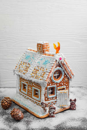 New Year Christmas gingerbread house decorated with icing sugar snow. Christmas figure Santa Claus, reindeer, snowman next to gingerbread house. Christmas rooster symbol of new year gingerbread house.