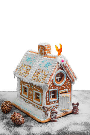 New Year Christmas gingerbread house with icing snow. Christmas figure Santa Claus, reindeer, snowman near gingerbread house. Christmas rooster symbol of new year gingerbread house. Isolated on white