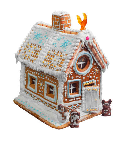 New Year Christmas gingerbread house decorated with icing sugar snow. Christmas figure Santa Claus, reindeer, snowman next to gingerbread house. Christmas rooster symbol of new year gingerbread house. Isolated on white Stock Photo