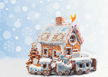 Assorted Christmas gingerbread cookies. Christmas gingerbread village, house, train, tree. Christmas New Years background with snowflakes. Christmas card with gingerbread village.