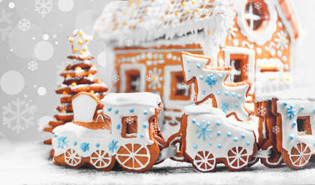 Christmas card. Assorted Christmas gingerbread cookies. Christmas gingerbread village, house, train, tree. Christmas New Years background with snowflakes. Christmas food gingerbread house, train, tree. Stock Photo