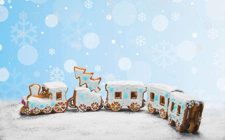 Koekjes van de peperkoek in de vorm van een trein. Kerstkoekjes trainen bedekt met poedersuiker. Kerstvakantie snoep Gingerbread Cookies trein. Nieuwjaarskaart met sneeuw, Kerstmis peperkoek cookies trein