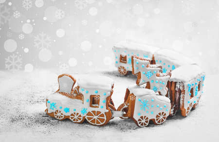New Year card with Christmas sweets toy. Gingerbread cookie in the form a Christmas train. Gingerbread Christmas tree on the train. Snow background with snowflakes, blue, white icing on steam train.