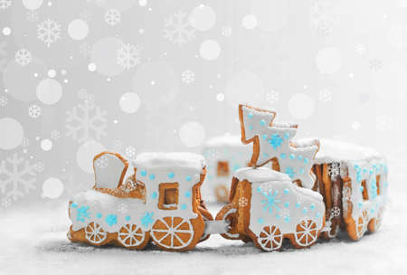 ngerbread Cookies in the form of train. Christmas cookies train covered with icing. Christmas Holidays sweets Gingerbread Cookies train.  New Year card with snow, Christmas gingerbread cookies train