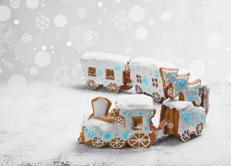 Gingerbread Cookies in the form of train. Christmas cookies train covered with white icing. Christmas Holidays sweets Gingerbread Cookies train.  New Year card with snow, Christmas gingerbread cookies train, white, blue.