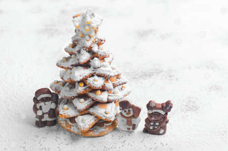an icing: New Year Christmas card. Gingerbread Christmas tree Cookies decorated with icing sugar and sweets. Christmas Chocolate Marzipan figure next to the gingerbread Christmas tree. Sweet snow. Blank space
