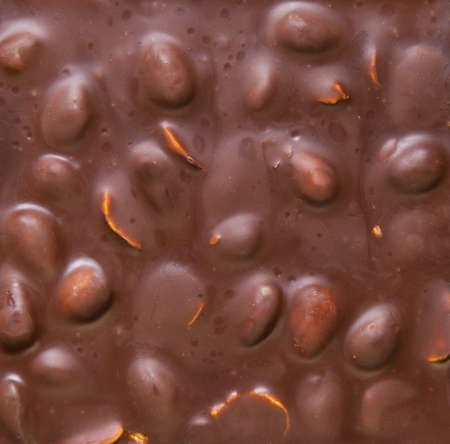 Texture of milk chocolate with nuts. Brown milk chocolate almonds nuts, background. Top view. Stock Photo