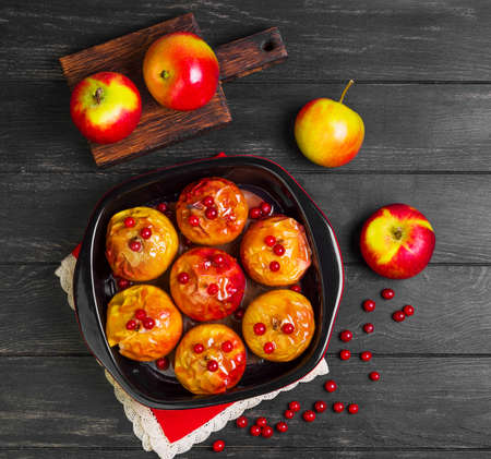 Baked apples baking in oven. Fresh apples for baking on board. Sauce for baked apples, red berries. Dark black wood background. Garden apples. Top view, blank space. Stock Photo