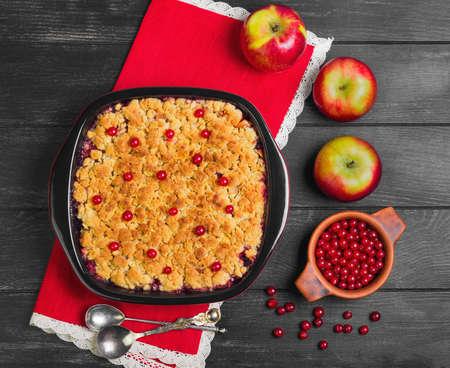Dessert pie crumble cake apples, red berries cranberries. Fresh apples, berries for  pie crumble cake, cloth. Red Black ceramic baking pan cake crumble. Wooden dark background. Top view.