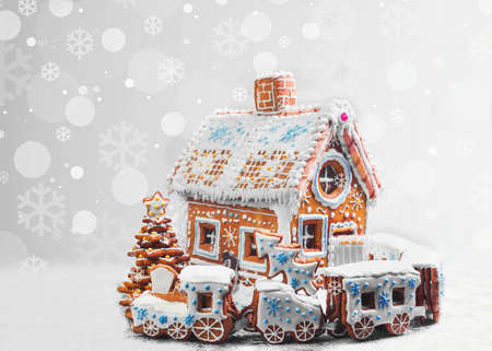 Assorted Christmas gingerbread cookies. Christmas gingerbread village, house, train, tree. Christmas New Year's background with snowflakes. Christmas card with gingerbread village. Stock Photo