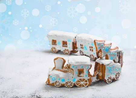 Gingerbread Cookies in the form of train. Christmas cookies train covered with icing. Christmas Holidays sweets Gingerbread Cookies train.  New Year card with snow, Christmas gingerbread cookies train