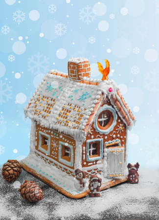 New Year Christmas gingerbread house decorated with icing sugar snow. Christmas figure Santa Claus, reindeer, snowman next to gingerbread house. Christmas rooster symbol of new year gingerbread house. Isolated on white 版權商用圖片