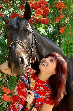 Brunette Female Model with Black Horse under Rowan tree Stock Photo
