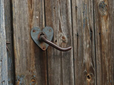 Aged door handle on wooden door