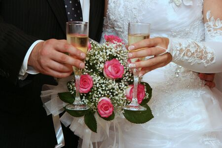 Female and male hands of newlyweds with champagne cups