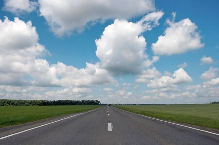 wide countryside asphalt road under cloudy blue sky panorama