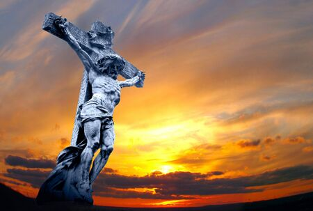 marble holy cross with crucified Jesus Christ against dramatic sunset