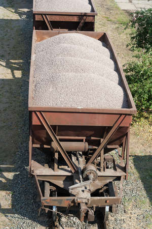 The old dirty cargo train with cars which are loaded by crushed stone.
