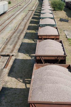 El viejo tren de carga sucia con los coches que se cargan por piedra triturada.