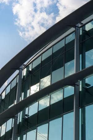 Edificio moderno. Wall. Platos de cristal que reflejan el cielo con nubes. Foto de archivo