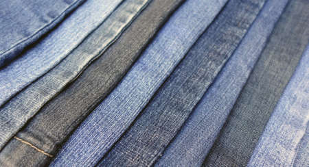 overlapped: Blurred denim pattern with various pairs of jeans overlapped in a diagonal pattern, blurry blue fabric background photo.