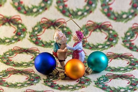 mrs santa claus: Santa and Mrs Claus Ornament on Wrapping Paper Backdrop Stock Photo