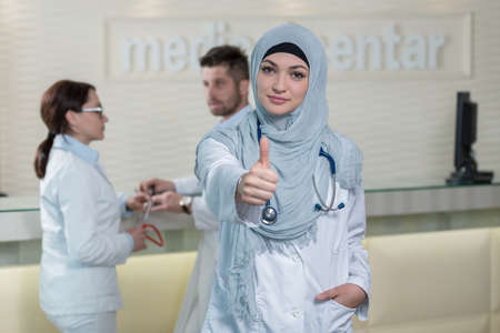 thumbup: Happy smiling cheerful female muslim doctor with thumbs up gesture. Stock Photo