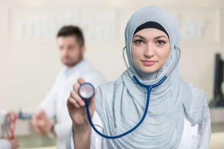 auscultate: Front view of an arab doctor woman showing stethoscope