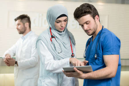 Saudi arab doctors working with a tablet.
