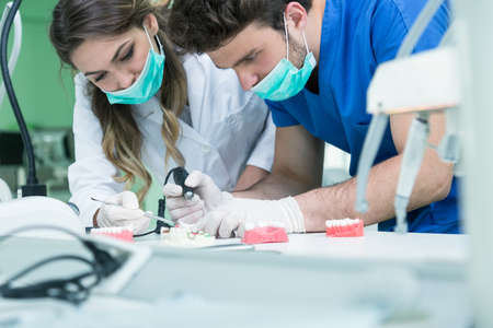 prosthetics: Dental prosthesis, dentures, prosthetics work. Prosthetics hands while working on the denture, false teeth, a study and a table with dental tools.