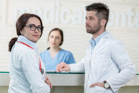 personal medico: Personal m�dico que tiene discusi�n en el pasillo del hospital moderno Foto de archivo