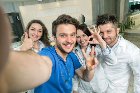four person only: Smiling Team Of Doctors And Nurses At Hospital Taking Selfie.