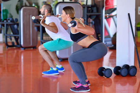 pushup: Gym man and woman push-up strength pushup with dumbbell in a workout