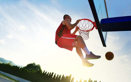 dunk: Young basketball player drives to the hoop for a high flying slam dunk in front of sunset sky Stock Photo