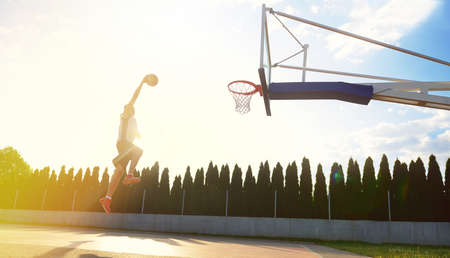 dunk: A young basketball player flying towards the rim for a slam dunk.