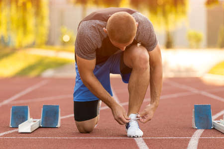 Female athlete tying laces for jogging. Woman jogging on a running track. running shoes. Fitness health.