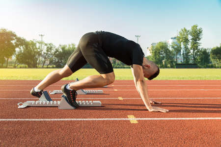 homme Athletic commencer le jogging du soir dans les rayons du soleil