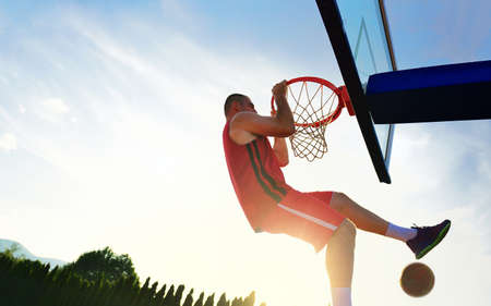 layup: Young basketball player drives to the hoop for a high flying slam dunk in front of sunset sky Stock Photo