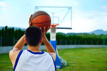 Rear view of a basketball player, shooting at basket outdoor.