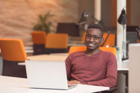 distant work: Handsome smiling successful African American man wearing formal suit, oval glasses, using laptop computer for distant work Stock Photo