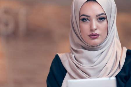 Jonge Arabische zakelijke vrouw draagt een hijab, werken in haar startup kantoor. Diversiteit, multiraciale begrip