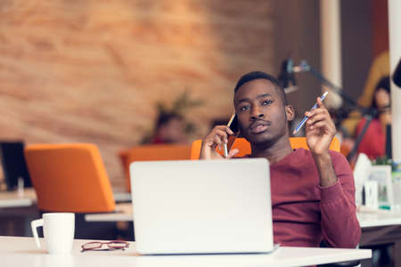 black professional: African American businessman on the phone sitting at the computer in his startup office Stock Photo