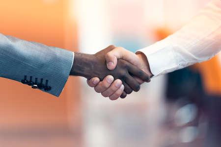 racismo: Apretón de manos entre africano y un hombre caucásico.