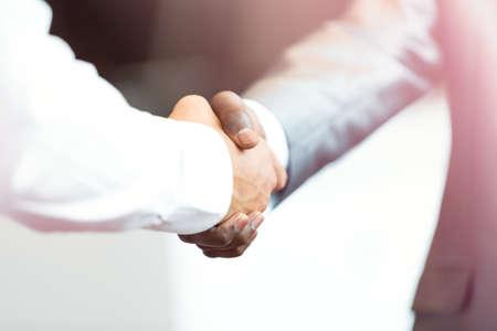 Handdruk tussen Afrikaanse en een blanke man.