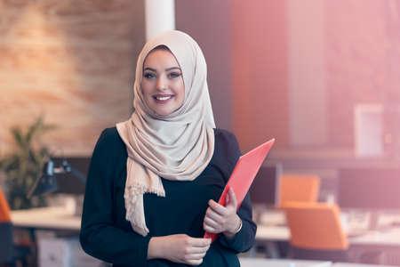 Arabische zakelijke vrouw met een map en praten aan de telefoon geïsoleerd op wit