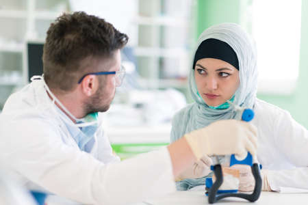 palate: Dental prosthesis, dentures, prosthetics work. Arab students with hijab while working on the denture, false teeth, a study and a table with dental tools