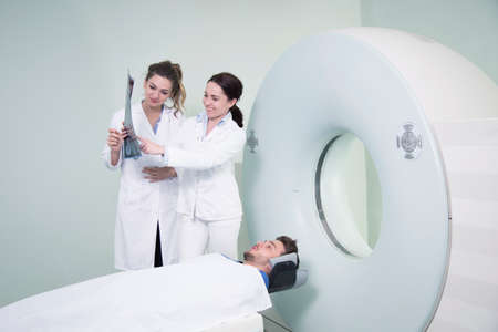 computed: Radiologic technician and Patient being scanned and diagnosed on CT (computed tomography) scanner in hospital.
