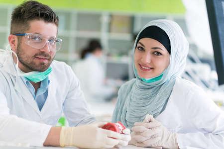 Dentale prothesen, kunstgebit, protheses werken. Arabische studenten met hijab tijdens het werken op de prothese, valse tanden, een studie en een tafel met tandhulpmiddelen