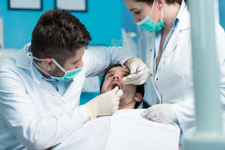 Dentistry education. Male dentist doctor teacher explaining treatment procedure to students group in dental clinic. Stock Photo