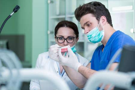 Dentale prothesen, kunstgebit, protheses werken. Protheses handen tijdens het werken op de prothese, valse tanden, een studie en een tafel met tandheelkundige instrumenten.